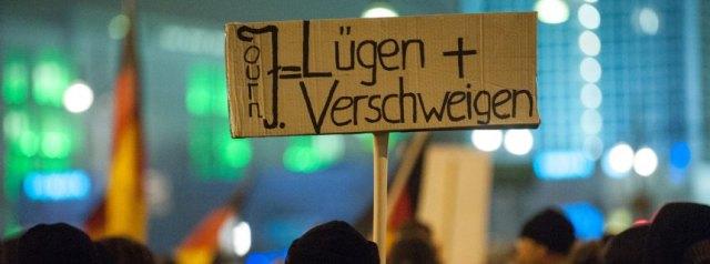 """Anhänger der islamkritischen Bewegung Bärgida (Berliner Patrioten gegen Islamisierung des Abendlandes) demonstrieren am 19.01.2015 in Berlin mit einem Schild """"Journ=Lügen+Verschweigen"""". Eine Terrordrohung von Islamisten gegen die Pegida-Bewegung (Patriotische Europäer gegen die Islamisierung des Abendlandes) hat zu einem Verbot für alle Versammlungen unter freiem Himmel in Dresden durch die Polizei für diesen Montag geführt. Foto: Paul Zinken/dpa +++(c) dpa - Bildfunk+++"""